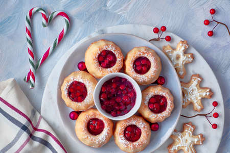 Mini bundt ring cakes with red whortleberry jam on light textured background with fir twigs, berries, cookies and candy canes. Christmas holiday sweet food.