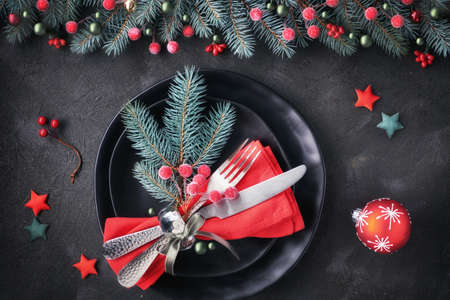 Christmas table setup on dark background. Flat lay with Xmas decorations in green and red with frosted berries, trinkets, black plates and crockery. 免版税图像