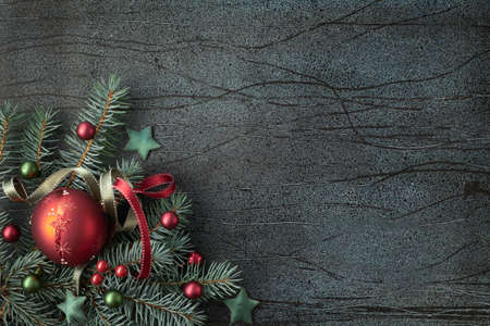 Christmas background with fir twigs and glass trinkets in green and burgundy on dark abstract background with text space
