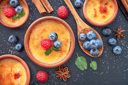 Creme brulee (cream brulee, burnt cream) with raspberry, blueberry and mint in terracota clay baking dishes. Top view, dark stone background. Stock Photo