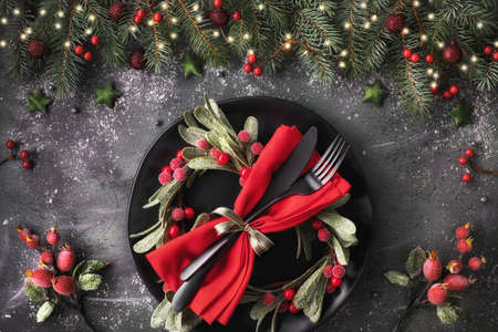 Christmas table setup on dark background. Flat lay with Xmas decorations in green and red with frosted berries, trinkets, black plates and crockery. Stock Photo
