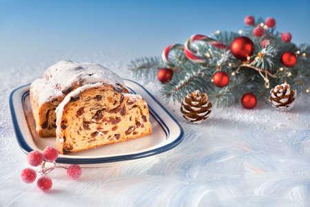 Christstollen auf weiß-blauem festlichen Hintergrund mit Tannenzweigen und Schmuckstücken. Traditionelles deutsches Dessert für Weihnachtsfeier, horizontales Bild mit Kopienraum.