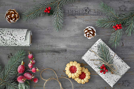 Christmas background with decorated fir twigs, jam cookies, wrapped gift and wrapping paper on rustic wooden background, top view