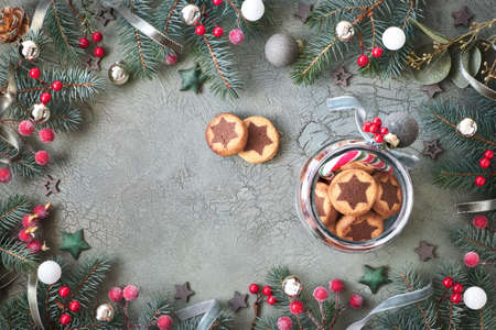 Jar of star cookies on green rustic background with decorated Christmas tree twigs, flat lay