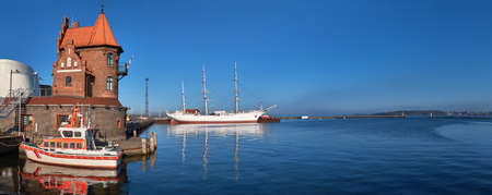 Rescue boat in front of historical brick building in Hafeninsel and historic sailship in Stralsund, Northern Germany, panoramic image 免版税图像