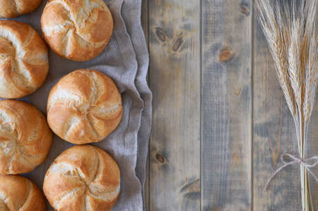 Crusty round bread rolls, known as Kaiser or Vienna rolls on linen towel on rustic wood, flat lay with copy-space Imagens