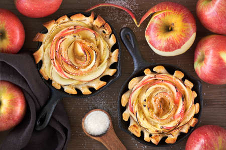 Homemade puff pastries with rose shaped apple slices baked in iron skillet. Top lay on wooden board with some apples and sugar