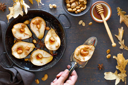 Flat lay with a tray of baked pears with caramelized nuts on dark wooden background with Autumn leaves, sugar, cinnamon and honey