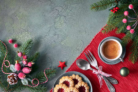 Flat lay with Xmas decorations in green and red with frosted berries and trinkets, coffee and Christmas cookies, text space