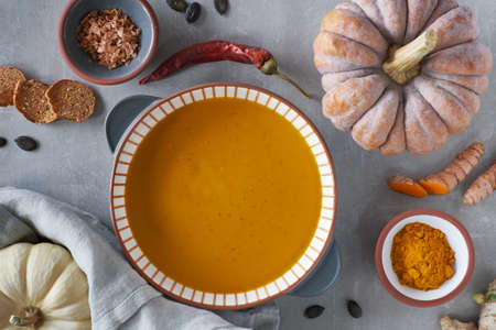 Pumpkin creme soup in stripy ceramic bowl surrounded by ingredients: pumpkin, cucruma, ginger, chili, oak salt flakes and pumpkin seeds. Top view, flat lay, space for your text in the middle Banco de Imagens