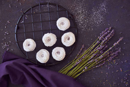 Flat lay with a plate of home-made marshmallows (zephyr, meringue) made with lavender on dark background 版權商用圖片
