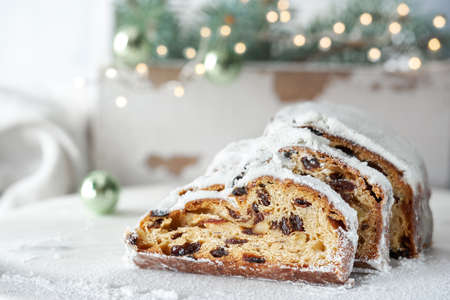 Christmas stollen on white festive background with fir twigs and trinkets. Traditional German dessert for Christmas celebration.