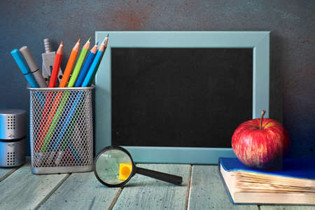 Stationery, apple and magnifying glass on wooden table in front of blackboard with text space