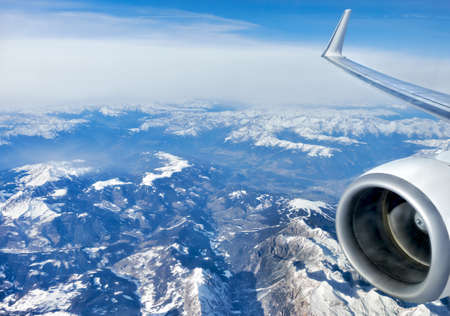 Alps under snow, aerial view from airplane with part of wing and a turbine