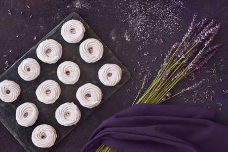 Flat lay with a plate of home-made marshmallows (zephyr, meringue) made with lavender on dark background Stock Photo