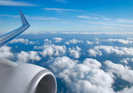 Aerial view of clouds, horison, blue sky and plane wing view through the airplane window.