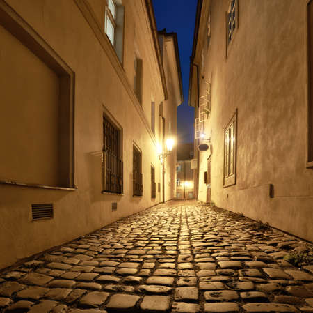 Old narrow street in Prague, Mala Strana, late in the evening with street lights reflected in cobblestones