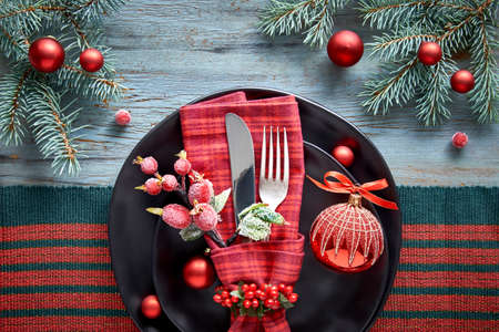 Flat lay with Xmas decorations in green and red with frosted berries, trinkets, plates and crockery, Christmas menu concept Stockfoto