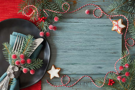 Flat lay with Christmas decorations in green and red with frosted berries and trinkets and black plate with crockery, text space
