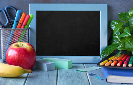 Stationery, apple and banana on a wooden table in front of blackboard with text space