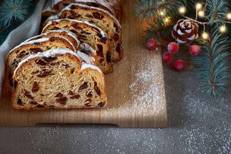 Christstollen auf dunkelfestlichem Hintergrund mit Tannenzweigen, Lichtern und Beeren. Nahaufnahme dieses traditionellen deutschen Desserts zur Weihnachtsfeier.