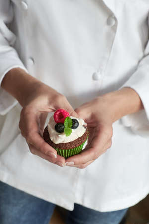 Close-up on hands of female pastry chef in white gown with muffin or a cupcake decorated with wild berries Archivio Fotografico