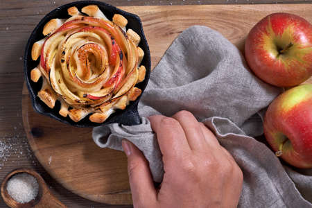 Homemade puff pastry with rose shaped apple slices baked in iron skillet. Hand holding skillet with the pastry with a towel. Top lay on wooden board with some apples and sugar.
