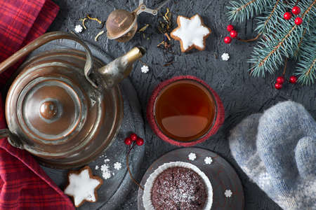 Chocolate muffins, tea cup, tea mesh on gray rustic backgrond with Christmas tree twigs decorated with red berries. Xmas background