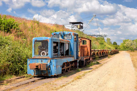 Old Rusty locomotive with a row of coal vagons and  bucket chain excavator outdoors in Brandenburg, Germany Zdjęcie Seryjne - 122372665