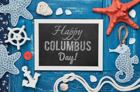 """Blank blackboard with sea shells, stones, rope and star fish on blue wooden background, text """"Happy Columbus day"""""""