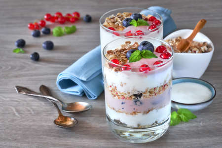Yogurt with muesli and berries, healthy dessert on neutral wooden table, text space
