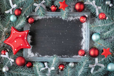 Green and red Christmas background with decorated chalk board. Decorated fir twigs around chalk board on rustic wood with snow. Top view with copy space.