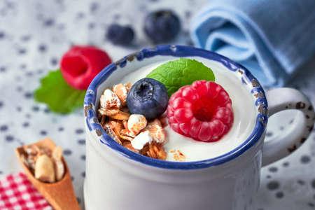 Yaourt au muesli, framboise et noix, dessert sain sur bois bleu clair avec plus de baies sur fond tacheté clair Banque d'images