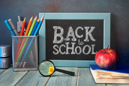 Stationery, apple and magnifying glass on wooden table in front of blackboard with text Back to school
