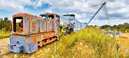 Old Rusty locomotive and bucket chain excavator and a row of coal vagons on a grass hill outdoors in Brandenburg, Germany Zdjęcie Seryjne