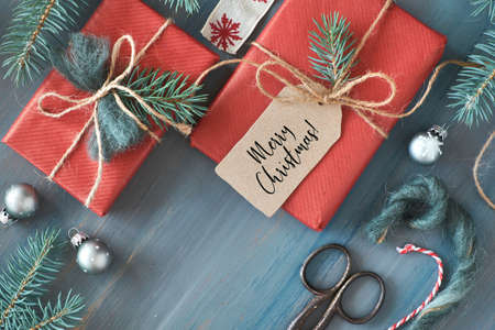 Rustic wooden background with fir branches and Christmas presents gift wrapped in red paper. Seasonal background shot from above. Flat lay, top view, text