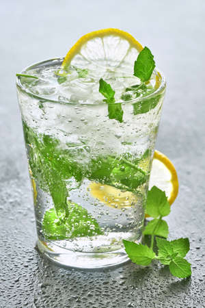 Close-up on a glass of sparkling water with lemon and mint on a grey stone background