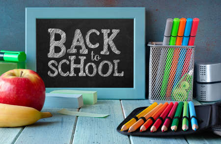 Stationery, apple and banana on a wooden table in front of blackboard with text Back to school Imagens