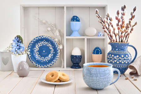 Cup of coffee and cookies on white table with bunch of pussy-willow in blue ceramic jar and matching springtime decorations