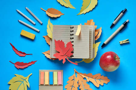 Autumn planning, open blank notebook with autumn leaves, pens, pencils, bookmarks and apple on blue background