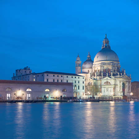 Romantic Venice background, illuminated church Santa Maria della Salute in Venice, Italy at night, square composition with copy-space Foto de archivo - 128298698