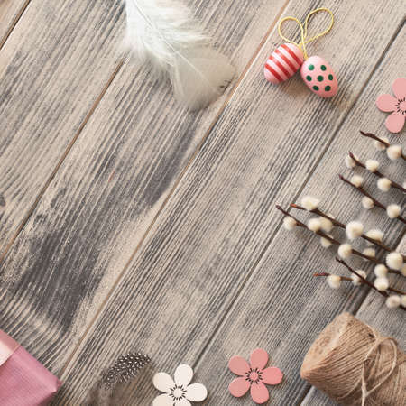 Flat lay with copy-space  on dark wooden surface with spring decorations: Easter eggs, wrapped gift box, colored feathers and pussy willow twigs, square composition Stock fotó