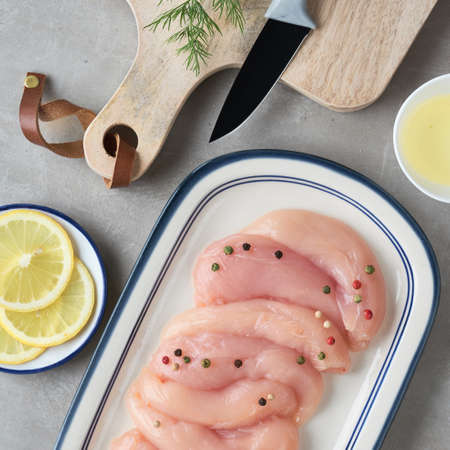 Raw chicken fillet. Meat with breadcrumbs, herbs , lemon and cooking oil. Top view on light stone background, square composition