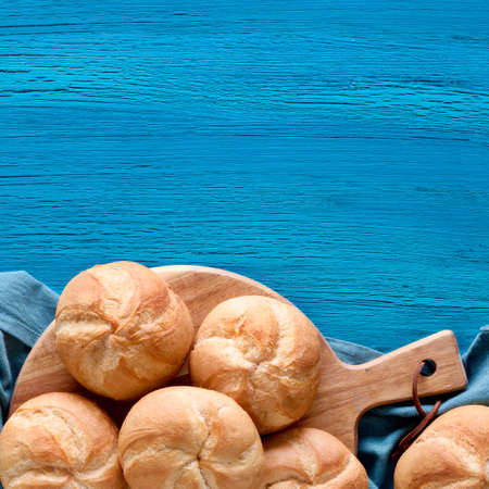 Crusty round bread rolls, known as Kaiser or Vienna rolls on linen towel. Flat lay on rustic background, square composition wiith copy-space 免版税图像