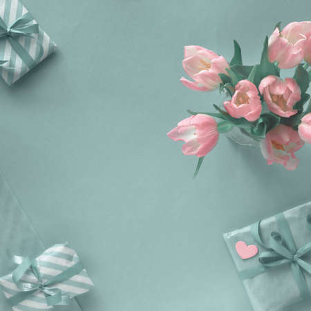 Blue background with pink tulips, stripy wrapping paper and wrapped gift boxes. Flat lay, square composition with copy-space