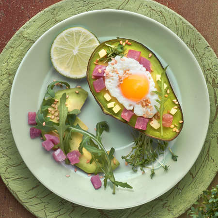 Keto diet dish: baked Avocado boat with ham cubes, quail egg and cheese served with green rucola salad. Top view of flat lay on green textured background, square composition