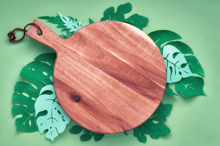 Floral background, flat lay with paper tropical leaves around wooden cutting board, copy-space