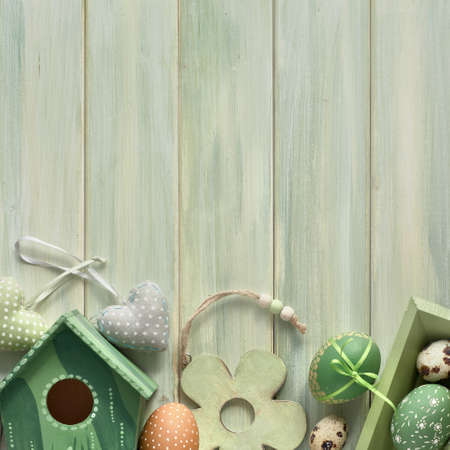 Easter flat lay on light green wooden planks with springtime decorations, eggs and nesting box, square composition with copy-space