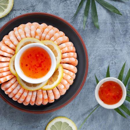 Crevettes épicées au citron et à l'ail servies sur une assiette sombre avec des citrons et une sauce chili douce, mise à plat sur fond sombre