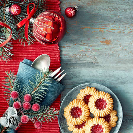 Flat lay with Xmas decorations in green and red with frosted berries and trinkets, coffee and Christmas cookies.Panoramic composition, lots of text space
